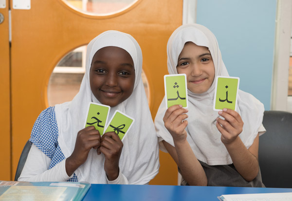 Two girls using language cards during an Arabic lesson.