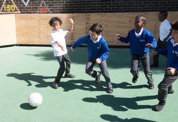 Boys playing football in the playground.