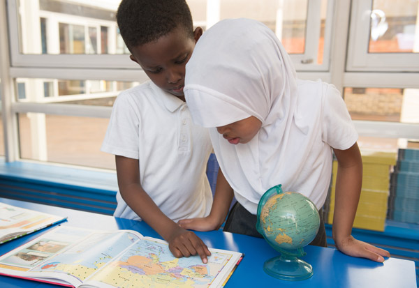 Boy and girl working through a world topic during a Geography lesson.