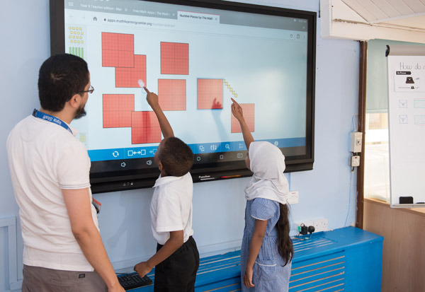 Teacher overseeing the use of the digital screen for a Maths lesson.