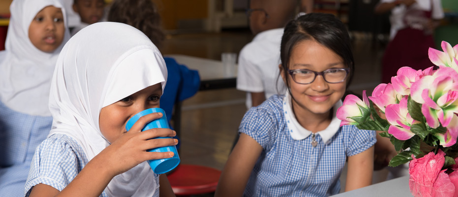 Two students relaxing having a drink of water.
