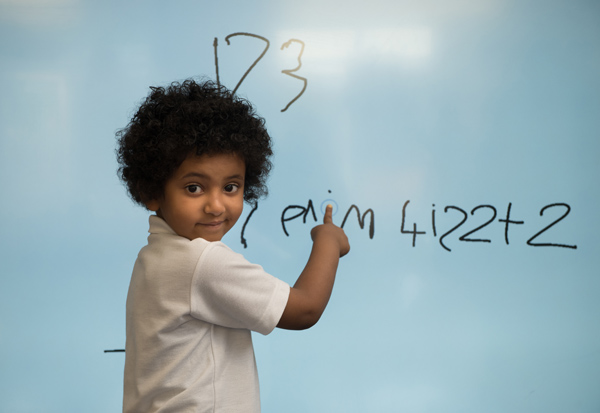 Young boy using the interactive digital screen for his Maths.