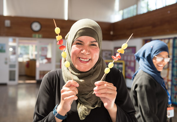 Happy teacher enjoying helping students make fresh fruit kebabs.