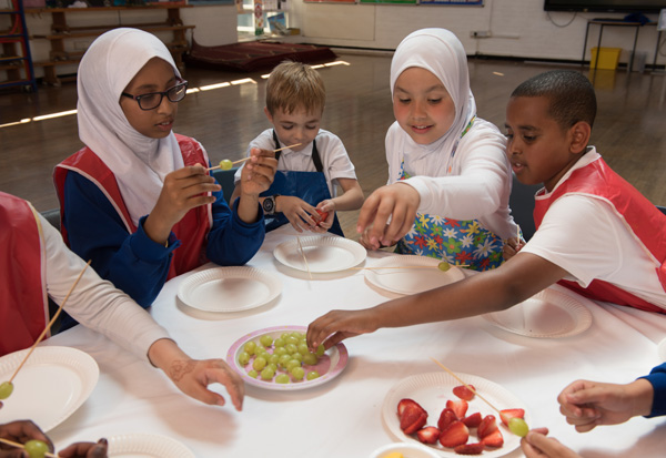 Students making fresh fruit kebabs.