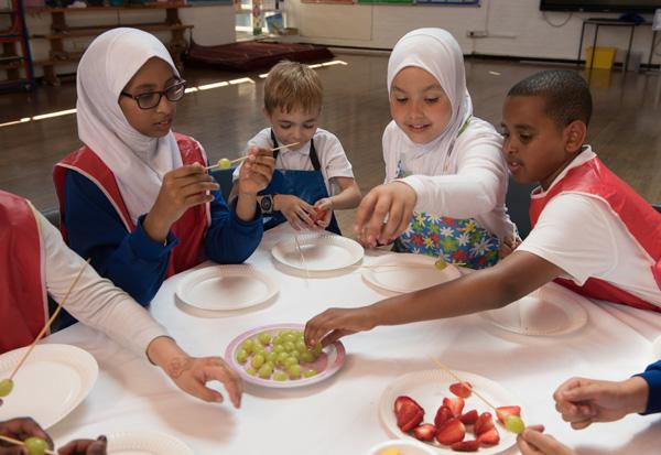Students making fresh fruit kebabs.