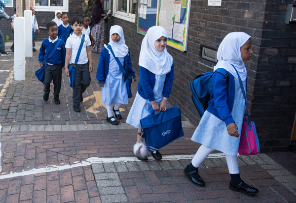 Students entering the school at the beginning of the day in their uniforms.