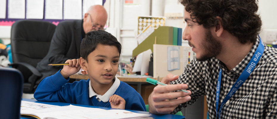 Young boy being helped by a teacher during an English lesson.